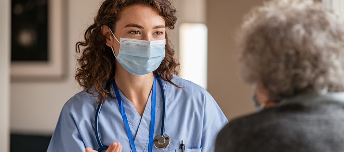 Female doctor nurse carer with mask talks to resident patient